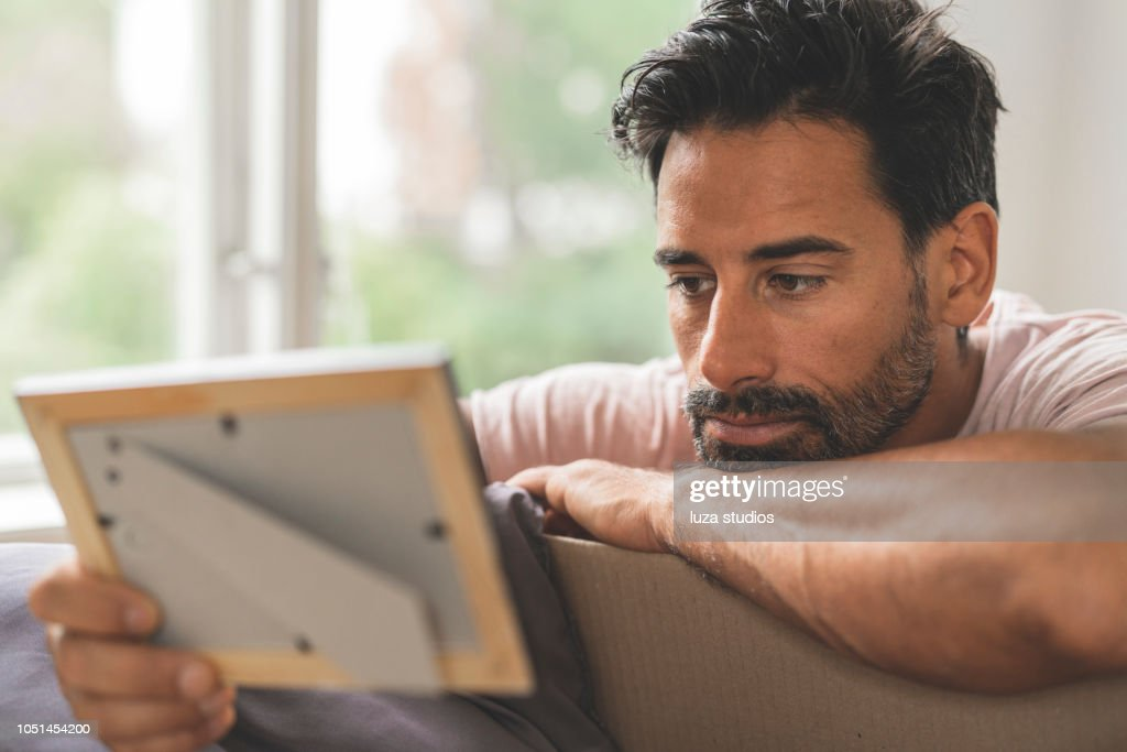 Man looking at old pictures while moving into a new house : Stock Photo
