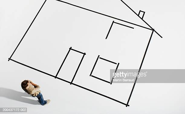 Man looking at outline of house on white ground, overhead view