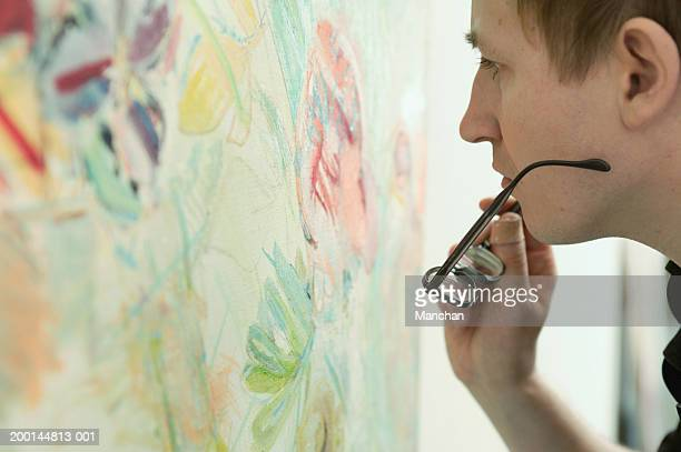 Man looking at painting, holding spectacles, close up, side view