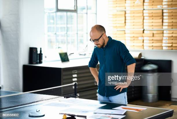 man looking at papers in modern office - arms akimbo stock photos and pictures