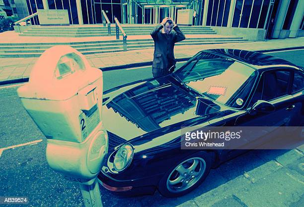 Man looking at parking ticket on car (wide angle lens, blue tone)