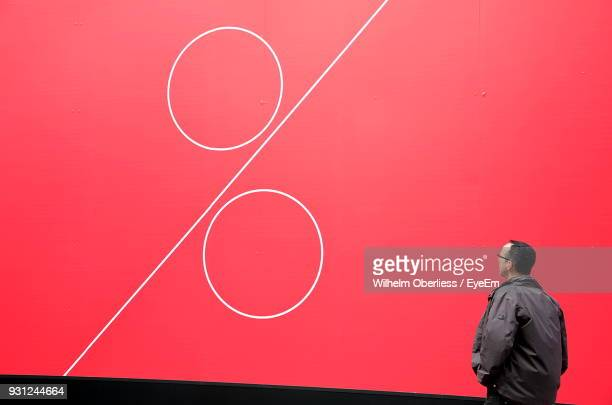 man looking at percentage sign on red wall - percentage sign stock pictures, royalty-free photos & images