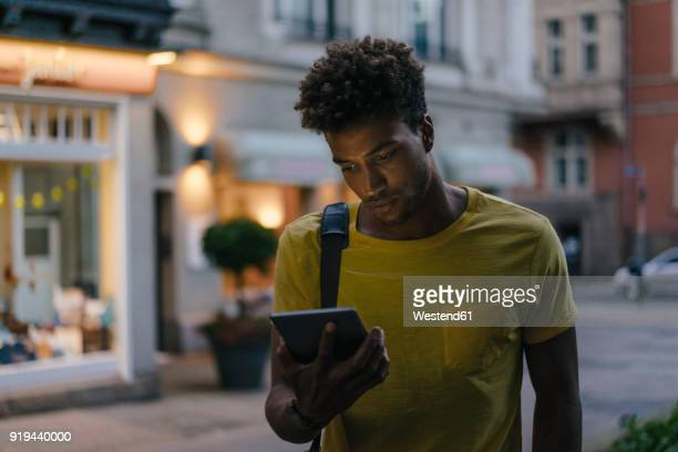 Man looking at phablet in the city at dusk