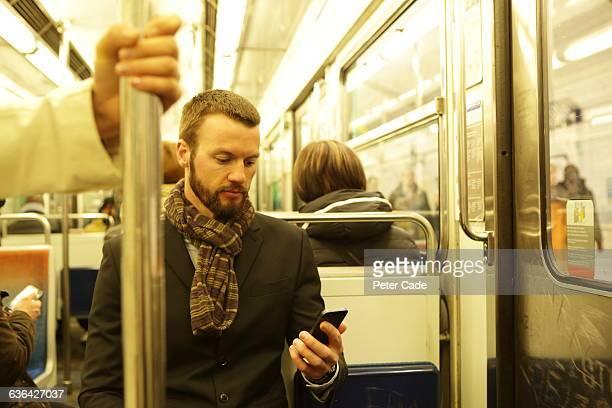 Man looking at phone on underground train