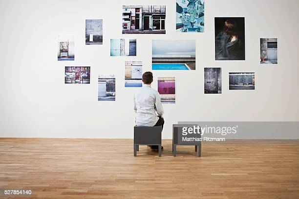 Man looking at photographs on wall