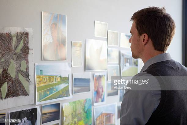 Man looking at pictures on wall