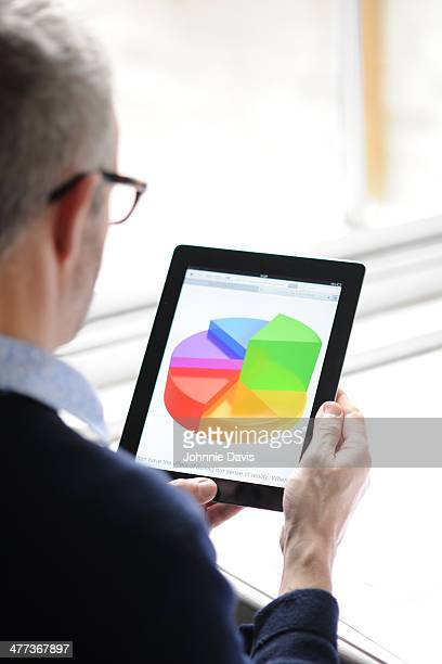 man looking at pie chart on tablet
