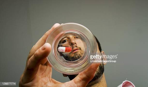 Man looking at pill at bottom of glass
