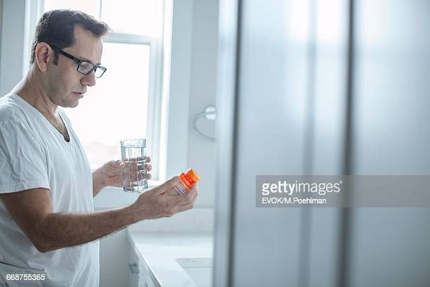 man looking at pills - taking a pill stock pictures, royalty-free photos & images