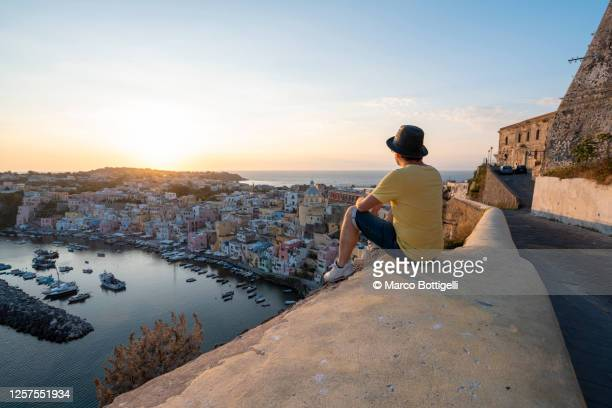 man looking at procida cityscape at sunset, gulf of naples, italy - holiday stock pictures, royalty-free photos & images
