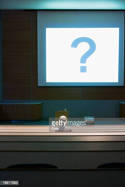 Man Looking at Question Mark in Classroom