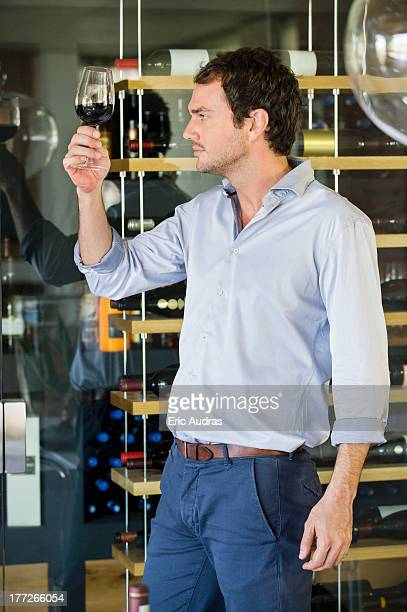 Man looking at red wine in a wineglass