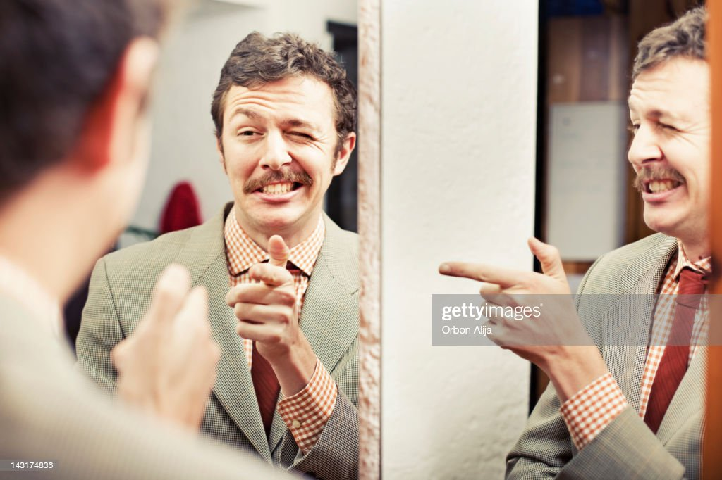 Man looking at reflection in mirror : Stock Photo