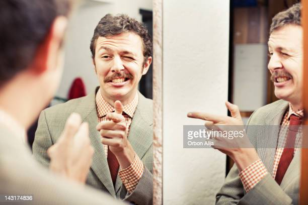 man looking at reflection in mirror - mirror stock photos and pictures
