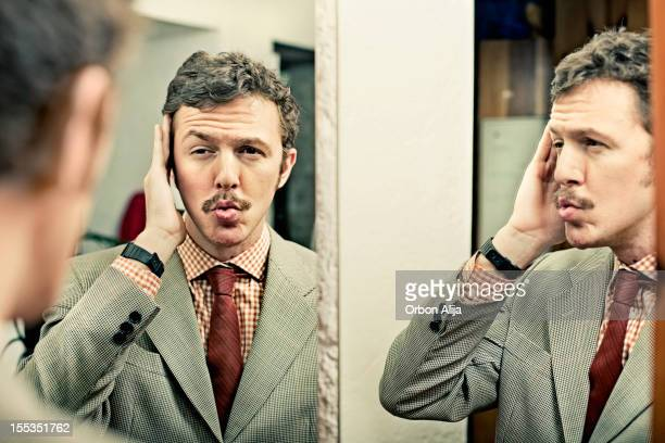 man looking at reflection in mirror - vanity stock pictures, royalty-free photos & images