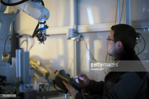 man looking at robot arm in a sensor technology plant - sensor stock pictures, royalty-free photos & images
