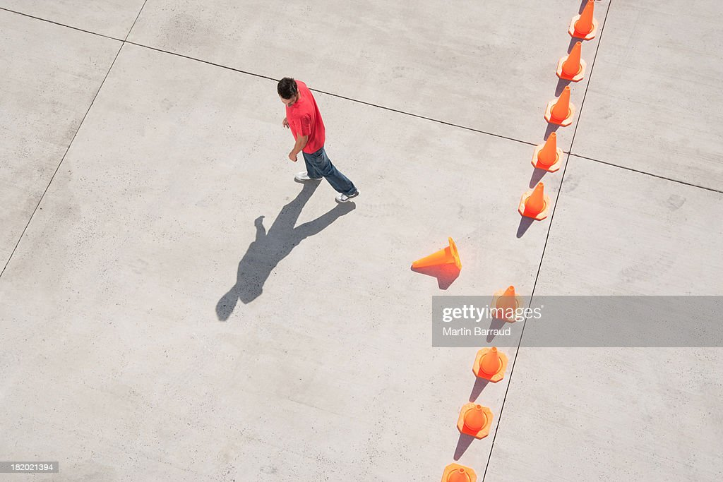 Man looking at row of traffic cones with one misplaced : Stock Photo