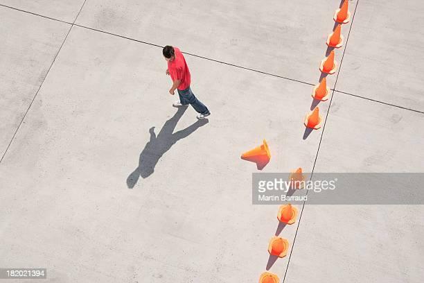 Hombre mirando a la fila de conos de tráfico con una fuera