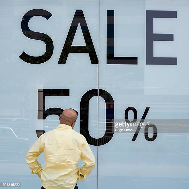 "man looking at ""sale"" sign - hugh sitton stock pictures, royalty-free photos & images"