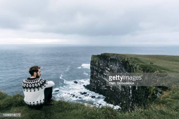 man looking at scenic view from the cliff in iceland - reykjavik stock pictures, royalty-free photos & images