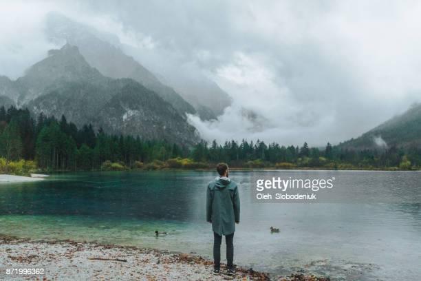 hombre mirando en el mirador del lago en los alpes mañana - gabardina ropa impermeable fotografías e imágenes de stock