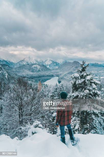Man looking at scenic  view of Schwansee  lake in Alps in winter