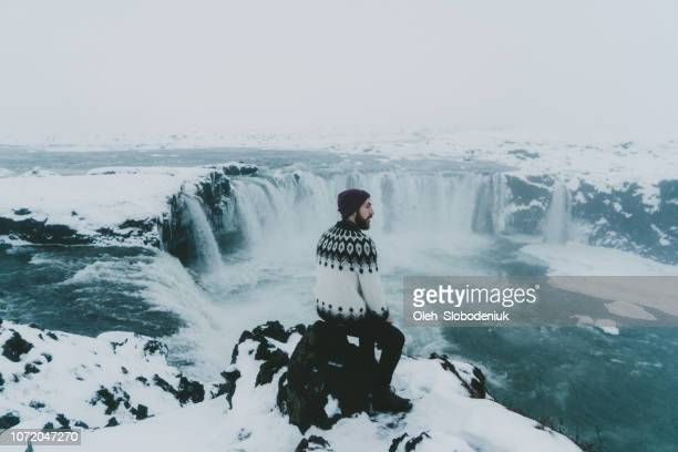 man looking at scenic view of waterfall in winter - skaftafell national park stock photos and pictures
