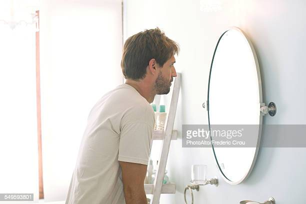 Man looking at self in bathroom mirror