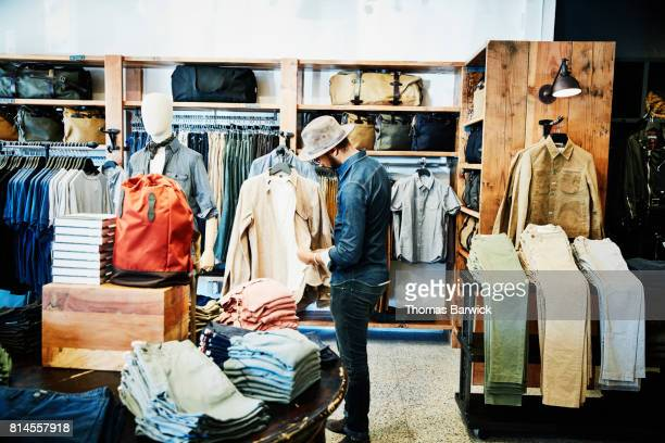 Man looking at shirt while shopping in mens clothing boutique