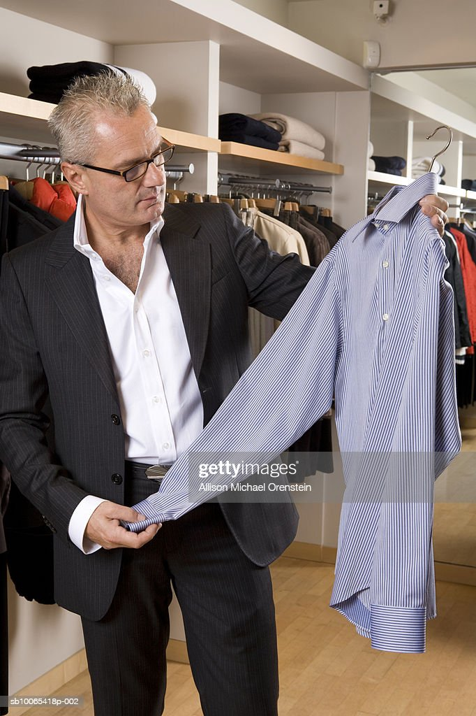 Man looking at shirts in clothing store : Foto stock