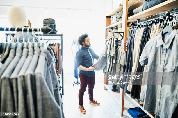Man looking at shirts while shopping in mens clothing boutique
