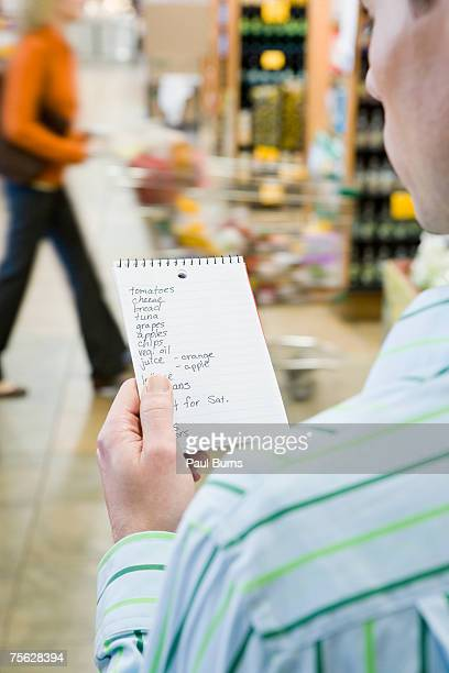 Man looking at shopping list in supermarket, over the shoulder view