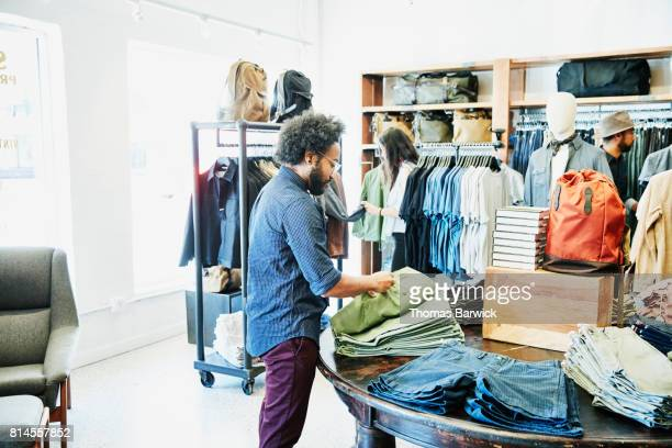 Man looking at shorts while shopping in mens clothing boutique
