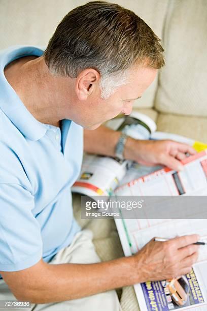 Homme à la recherche dans les petites annonces publicitaires dans un magazine