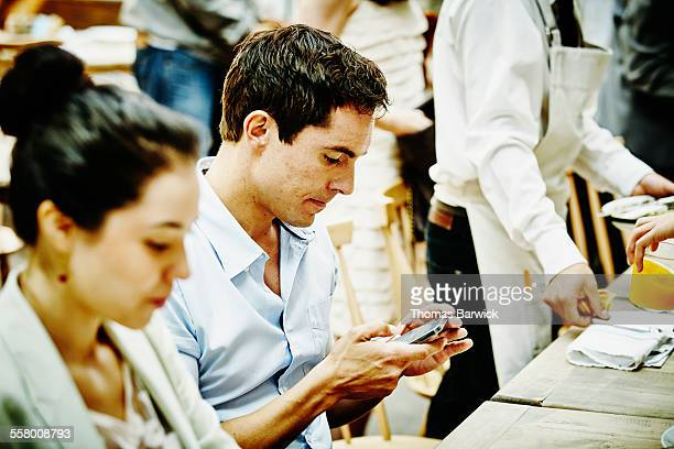 Man looking at smartphone during family dinner