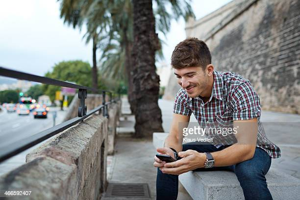 Man looking at smartphone, sitting on bench