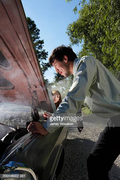 Man looking at smoking car engine on country road, woman in background