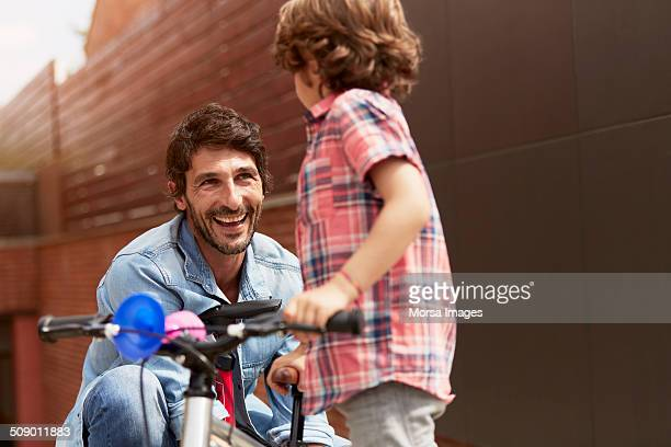 Man looking at son with bicycle