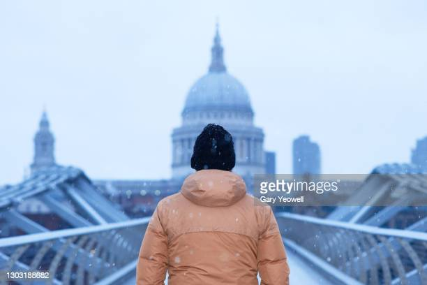 man looking at st paul's cathedral in snow - tourism stock pictures, royalty-free photos & images