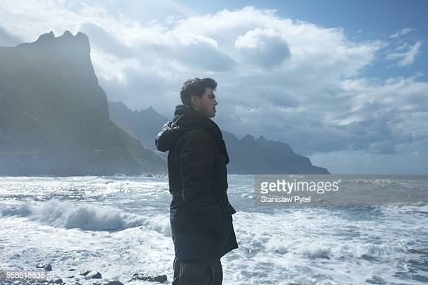 Man looking at stormy sea, cliffs in background