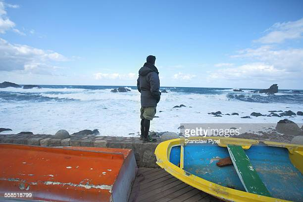 Man looking at stormy sea near colorful boats