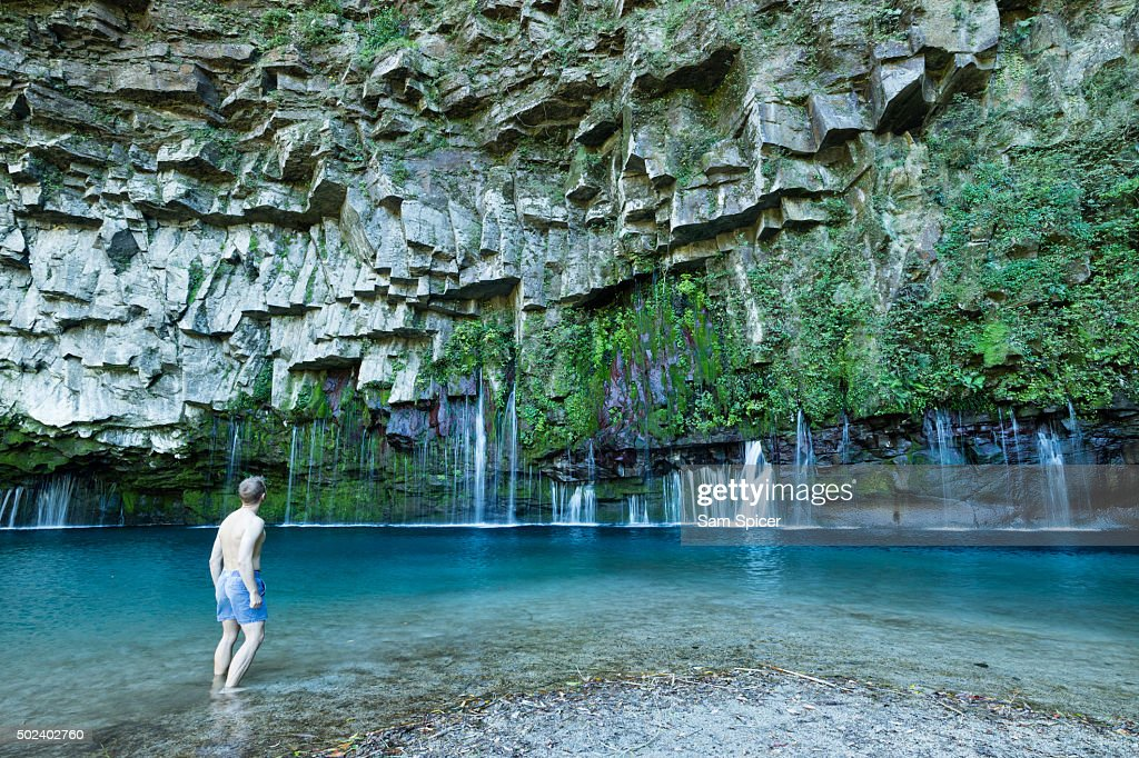 Man looking at stunning waterfall with columnar jointed basalt rocks and clear turquoise lagoon water, Kyushu, Japan : Stock Photo