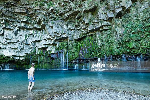 Man looking at stunning waterfall with columnar jointed basalt rocks and clear turquoise lagoon water, Kyushu, Japan