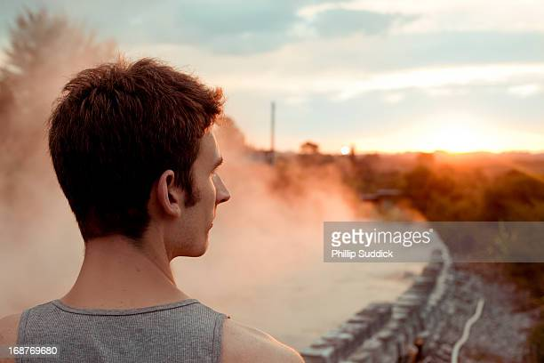 man looking at sunsetting on horizon over hot pool