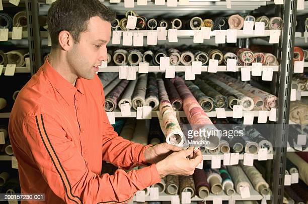 Man looking at tags attached to rolls of fabric on shelf