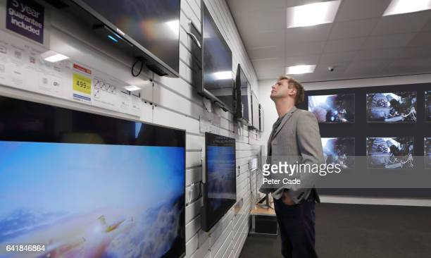 Man looking at televisions in shop