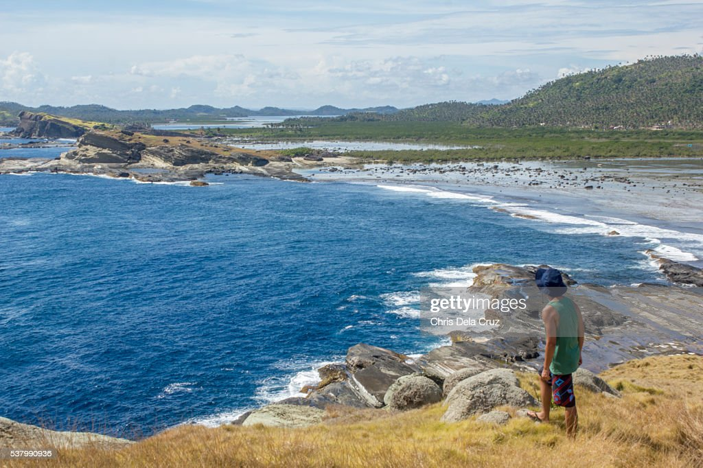 Man looking at the beach front on top of Macadlaw rock formation : Stock Photo