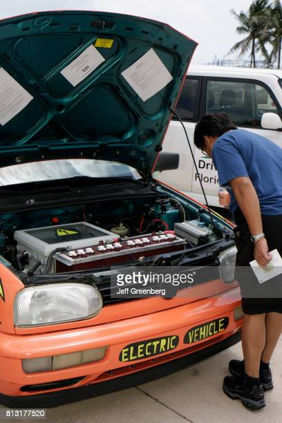 A man looking at the engine compartment of an electric vehicle at the Miami Goin' Green event