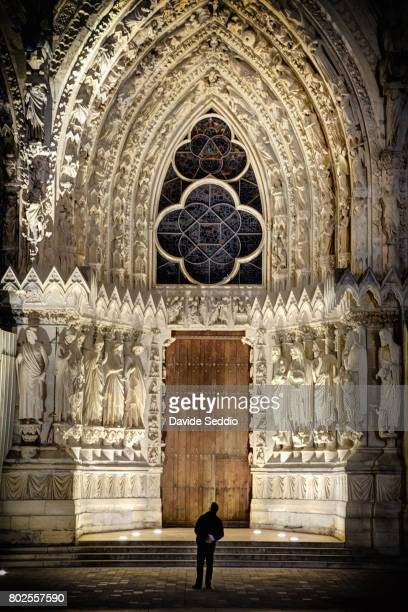 man looking at the main entrance door of the cathedral of notre dame de reims - ardennes department france stock photos and pictures