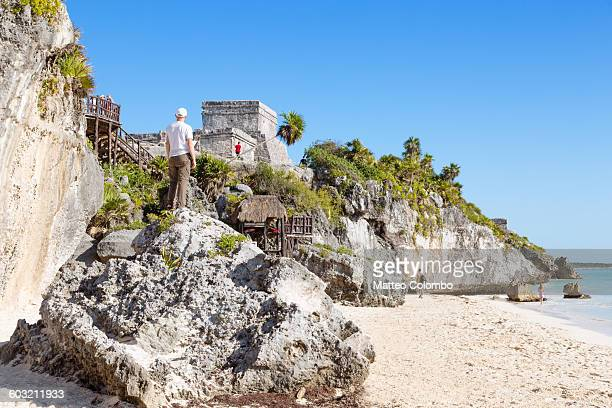 man looking at the old ruins of tulum, mexico - tulum mexico stock photos and pictures